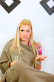 Ill woman sitting wrapped in woolen plaid with glass of water an — Stockfoto
