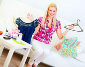 Smiling young woman sitting on sofa and choosing clothes — Stock Photo