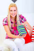 Lovely woman sitting on sofa and holding shopping bags in hands — Stock Photo
