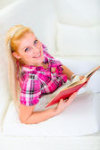 Smiling pretty woman relaxing on sofa and reading book — ストック写真