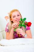 Sonriente a joven tirado en el sofá blanco con rosas rojas en la mano — Foto de Stock