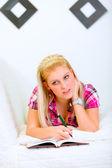 Zamyšlený mladá žena leží na pohovce s Poznámkový blok a pero — Stock fotografie