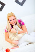 Portrait of beautiful young woman sitting on sofa with pillow in — Stock fotografie