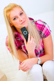 Portrait of happy young woman with TV remote control — Stok fotoğraf