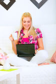 Happy modern housewife sitting on sofa with laptop and cup of co — Stock Photo