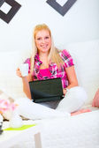 Smiling young woman sitting on couch with laptop and cup of coff — Stock Photo