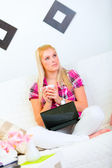 Thoughtful young female sitting on divan with laptop and cup of — Foto de Stock