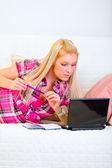 Jolie jeune femme couché sur le canapé avec le bloc-notes et stylo et look — Photo