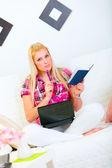 Gentil jeune femme assise sur le canapé avec le portable, bloc-notes et stylo — Photo