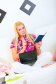 Thoughtful young woman sitting on couch with laptop, notepad and pen — Stock Photo