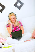 Happy young woman sitting on sofa with laptop and listening musi — Stock Photo