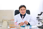 Smiling medical doctor sitting at table in office — Stock Photo