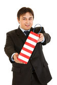 Smiling young businessman giving shopping bag — Stock Photo