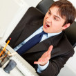 Stressful businessman sitting at office desk and looking at computer monito — Stock Photo
