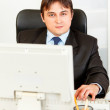 Stock Photo: Modern businessmsitting at office desk and working on pc