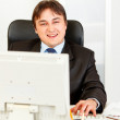 Smiling businessmsitting at office desk and working on pc — Stock Photo #8580382