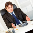 Displeased businessman sitting at office desk and waiting important phone c — Stock Photo #8580469