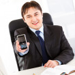 Smiling businessman sitting at office desk and holding mobile phone with b — Stock Photo