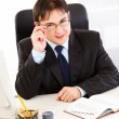 Smiling businessman sitting at office desk and straightening eyeglasses — Stock Photo #8580504