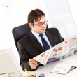 Modern businessman sitting at office desk and reading newspaper — Stock Photo #8580516