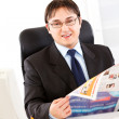 Smiling businessman sitting at office desk and holding newspaper in hands — Stock Photo #8580519