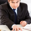 Concentrated businessman sitting at office desk and giving money packs — Stock Photo #8580528