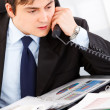 Concentrated businessman sitting at office desk and talking on phone — Stock Photo