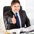 Pleased businessman sitting at office desk and showing thumbs up gesture — Stock Photo