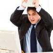 Angry  businessman sitting at office desk and destroying computer using key - Stock Photo