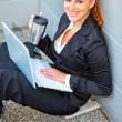 Royalty-Free Stock Photo: Smiling business woman with laptop and cup sitting on floor at office build