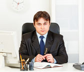 Serious modern businessman looking at camera sitting in office — Stock Photo