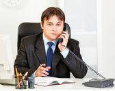 Thoughtful modern businessman talking on phone and making notes in diary — Stock Photo