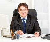 Smiling modern businessman sitting at office desk — Stock Photo