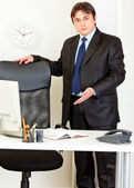 Friendly modern businessman inviting to sit on office chair — Stock Photo