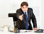 Friendly modern businessman standing at office desk and stretches out hand — Stock Photo