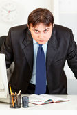 Strict modern businessman standing near office desk — Stock Photo