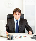 Dissatisfied modern businessman banging fist on table — Stock Photo
