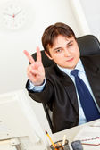 Smiling elegant businessman sitting at office desk and showing victory gest — Stock Photo