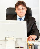 Modern businessman sitting at office desk and working on pc — Stock Photo
