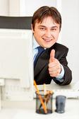 Usmívající se podnikatel při pohledu od monitoru a ukazuje palec nahoru gesto — Stock fotografie