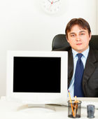 Modern businessman sitting at office desk and showing monitors blank screen — Stock Photo