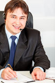 Smiling businessman with headset sitting at office desk and taking notes — Stock Photo