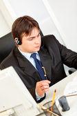 Серьезный бизнесмен с шлемофоном Сев на офисном столе и проверка Тимет — Стоковое фото