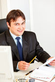 Smiling businessman sitting at office desk and working with documents — Stock Photo