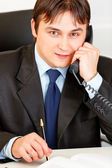Smiling modern businessman sitting at office desk and talking on phone — Stock Photo