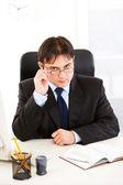 Авторитетный бизнесмен сидя на офисный стол и выпрямление волос eyeglas — Стоковое фото
