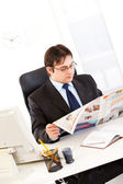 Modern businessman sitting at office desk and reading newspaper — Stock Photo
