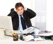Stressful businessman sitting at office desk being overloaded with loads — Stock Photo