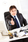 Successful businessman sitting at office desk and showing thumbs up gesture — Stock Photo