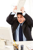 Angry businessman sitting at office desk and destroying computer using key — Stock Photo